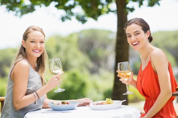 Heureux amis tenant des verres de vin dans un restaurant