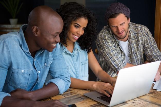 Heureux amis utilisant un ordinateur portable à table en bois dans un café