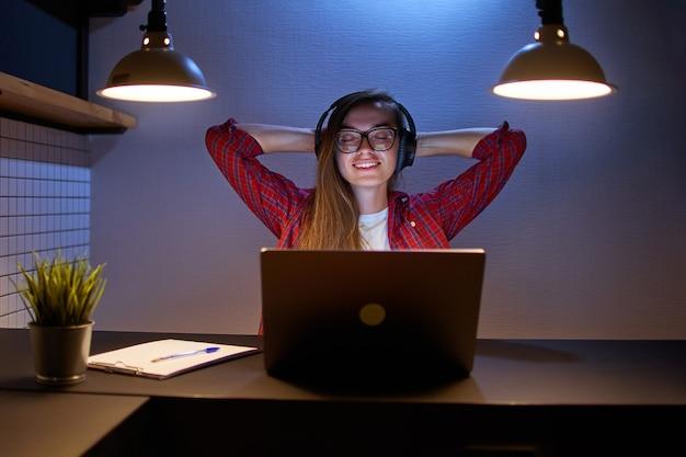 Heureux amoureux de la musique joyeuse femme satisfaite dans des écouteurs sans fil avec les mains derrière la tête en appréciant et en écoutant de la musique relaxante en ligne à l'aide d'un ordinateur portable