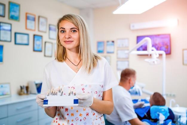 Heureux assistant dentiste souriant avec jeu de couleur des dents