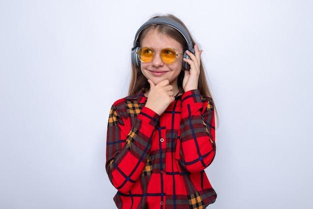 Heureux attrapé le menton belle petite fille portant une chemise rouge et des lunettes avec des écouteurs isolés sur un mur blanc