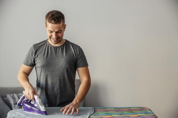 Heureux d'avoir aidé. un homme dans une pièce fermée se lève et cuit des vêtements avec un fer à repasser électrique chaud.