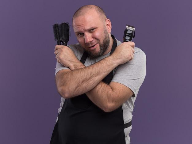 Heureux barbier masculin d'âge moyen en uniforme tenant un peigne avec une tondeuse à cheveux sur les épaules isolée sur un mur violet