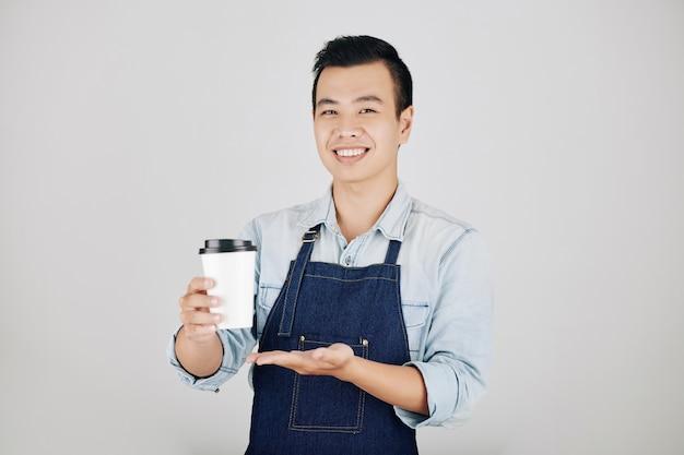 Heureux barista offrant une tasse de café