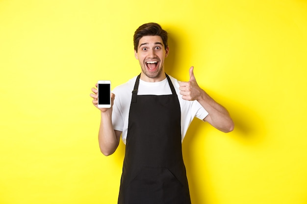 Heureux barista en tablier noir montrant l'écran du smartphone, faire un pouce vers le haut, recommander une application de café, debout sur fond jaune