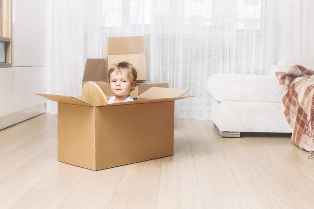 Heureux et beau bébé souriant à la maison dans le salon assis dans une boîte en carton