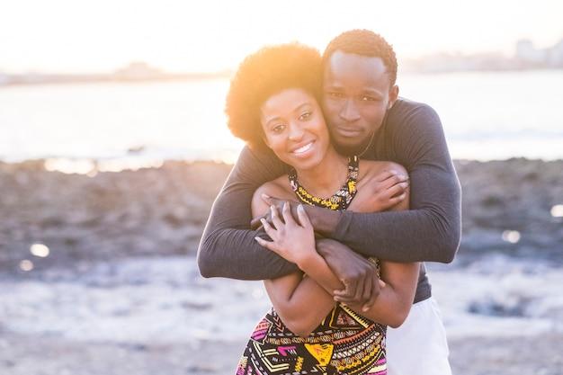 Heureux beau couple africain de race noire amoureux ou amitié rester ensemble marchant étreint avec de grands smileys sous la lumière du soleil de l'été en vacances ou style de vie dans leur ville