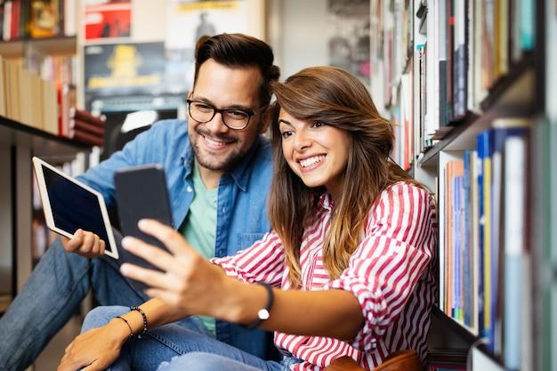 Heureux beau couple d'étudiants d'amour hipster prenant un selfie dans la bibliothèque de l'école.