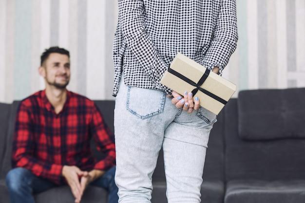 Heureux beau couple, une femme donne à un homme un cadeau pour les vacances à la maison ensemble