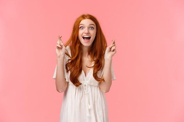 Heureux beau, heureux, excité rousse caucasienne fille voyant son rêve devenu réalité après avoir prié avec les doigts croisés, l'air étonné et surpris, réjouissez-vous du souhait réalisé, mur rose