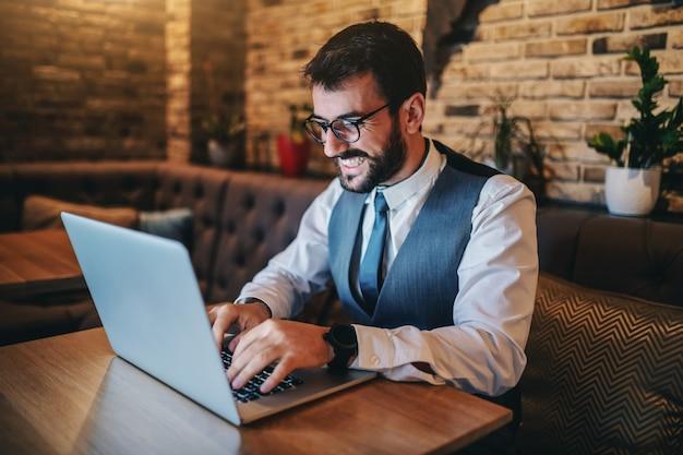 Heureux beau homme d'affaires caucasien barbu dédié en costume et avec des lunettes assis dans un café et utilisant un ordinateur portable pour le travail.