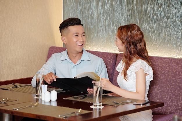 Heureux beau jeune homme assis à la table du café avec sa petite amie, lisant le menu et discutant de ce qu'il faut commander