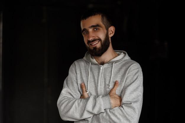 Heureux beau jeune homme avec une barbe souriant dans un sweat à capuche gris posant sur un mur sombre