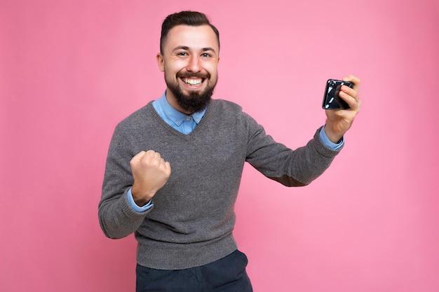 Heureux beau jeune homme non rasé brune avec barbe portant un pull gris et bleu tous les jours