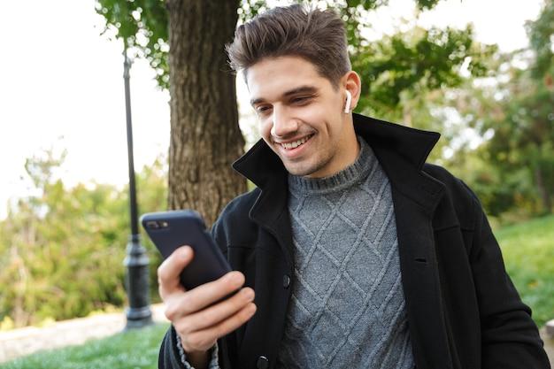 Heureux beau jeune homme optimiste en vêtements décontractés marchant à l'extérieur dans un parc verdoyant à l'aide de téléphone portable écoutant de la musique avec des écouteurs.