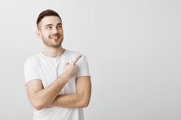 Heureux beau jeune homme en t-shirt blanc pointant le doigt dans le coin supérieur droit