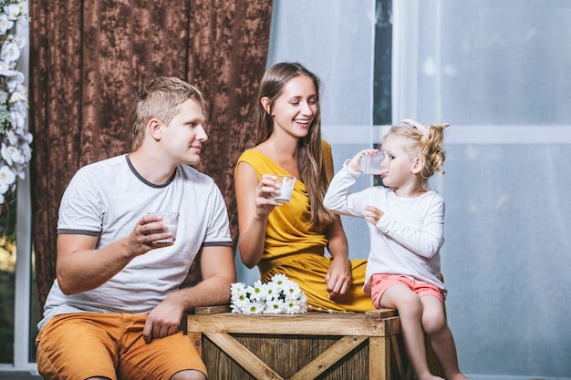 Heureux beau jeune père de famille, mère et fille boivent du lait et jouent ensemble dans la maison de pique-nique