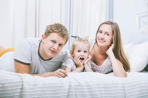Heureux beau jeune père de famille, mode mère et fille souriant ensemble à la maison
