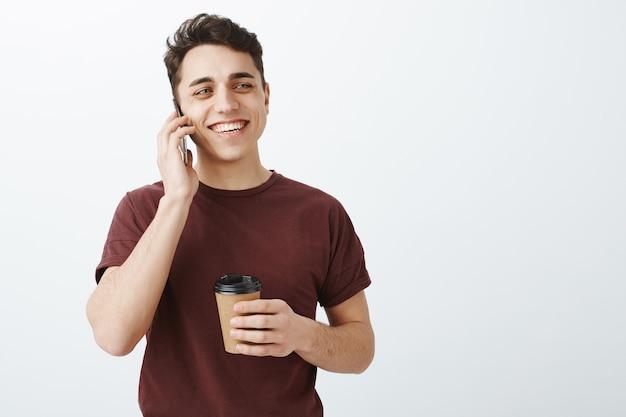 Heureux beau mâle en t-shirt rouge parlant par téléphone