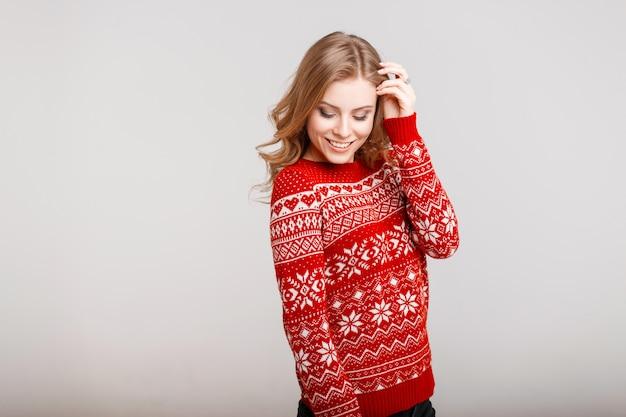 Heureux beau modèle femme en pull rouge avec ornement