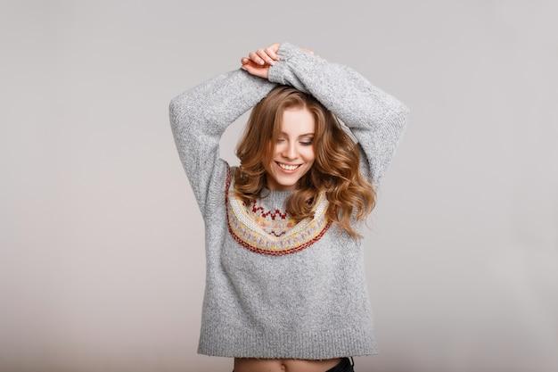 Heureux beau modèle femme en pull vintage qui pose en studio