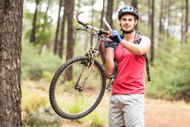 Heureux beau motard tenant un vélo et regardant la caméra
