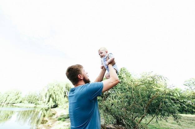 Heureux beau papa, père tenant bébé garçon en vêtements bleus