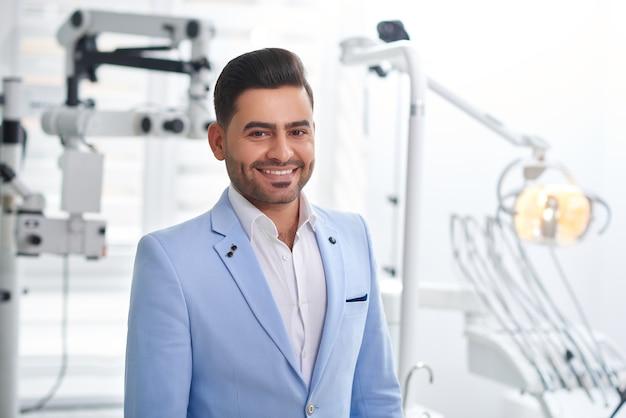 Heureux beau patient masculin souriant posant au bureau du dentiste