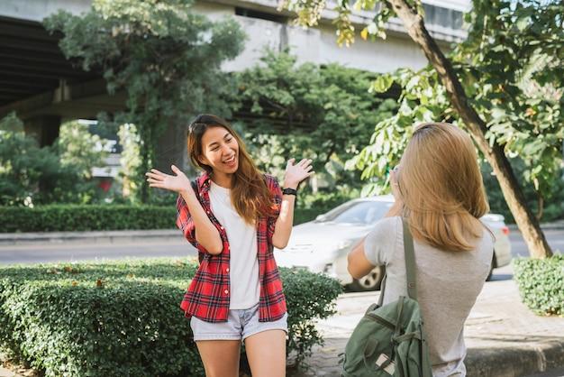 Heureux beau voyageur asiatique ami femme porte un sac à dos