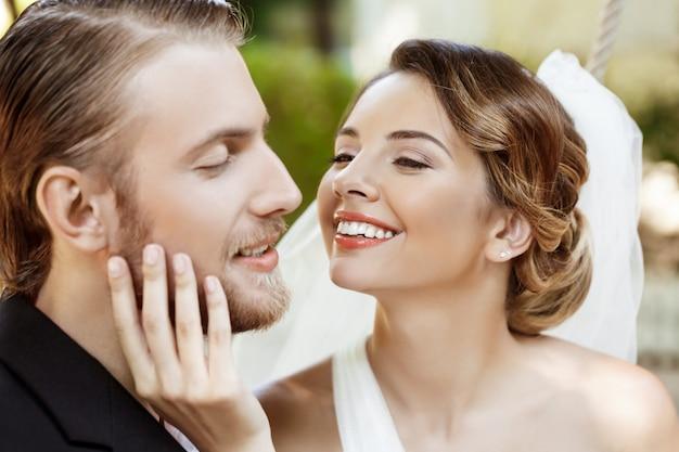 Heureux beaux mariés en costume et robe de mariée souriant, appréciant.