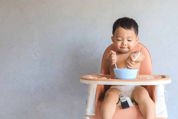 Heureux bébé asiatique bébé garçon assis sur une chaise haute pour bébé et manger de la nourriture par lui-même avec copie espace.