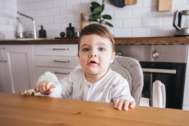Heureux bébé assis dans une chaise haute et riant dans une cuisine blanche moderne. une alimentation saine pour les enfants. vue de côté mignon enfant en bas âge