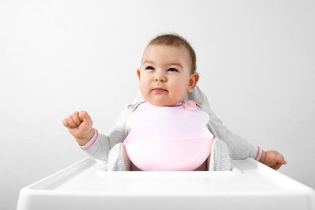 Heureux bébé bambin sur une chaise haute avec une cuillère à la main
