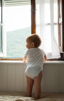 Heureux bébé blond assis sur un lit jouant et regardant par la fenêtre à la maison