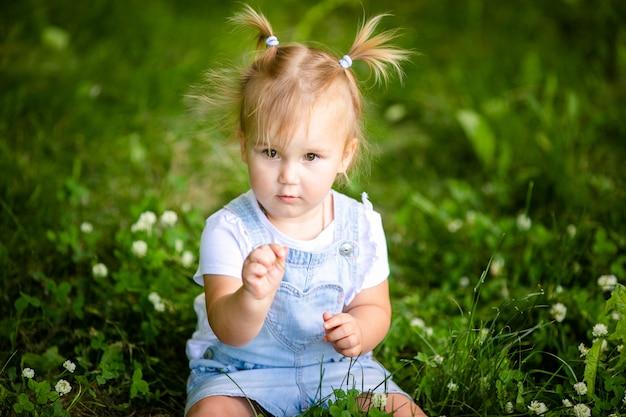 Heureux bébé fille blonde drôle avec deux petites tresses
