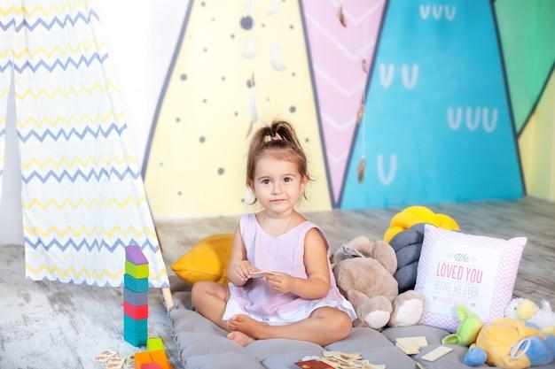 Heureux bébé joue dans la tente dans la chambre des enfants avec des jouets éducatifs enfant joue au wigwam avec des briques de jouets