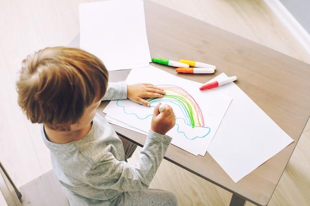 Heureux bébé mignon et beau souriant à la maison dessinant à la table dans la pépinière
