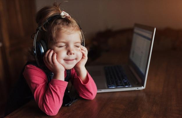 Heureux bel enfant dans les écouteurs, écouter de la musique