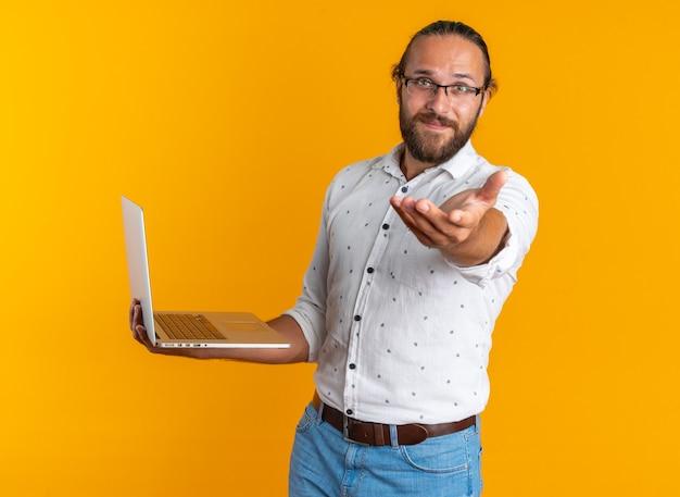 Heureux bel homme adulte portant des lunettes tenant un ordinateur portable tendant la main vers la caméra