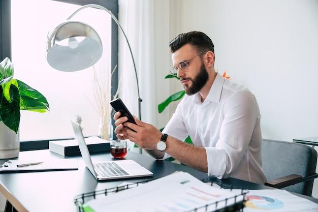 Heureux bel homme d'affaires barbu élégant et moderne dans des verres et une chemise blanche travaille sur l'ordinateur portable et le téléphone smert sur le bureau du lieu de travail de bureau.