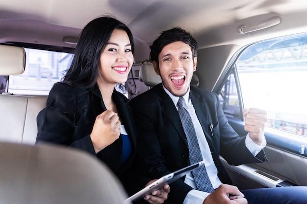 Heureux bel homme d'affaires et femme d'affaires assis dans la voiture de luxe limousine, travaillant sur ordinateur portable, fonctionne à tout moment et n'importe où concept.