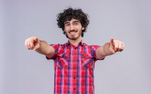 Un heureux bel homme aux cheveux bouclés en chemise à carreaux pointant avec l'index à la caméra