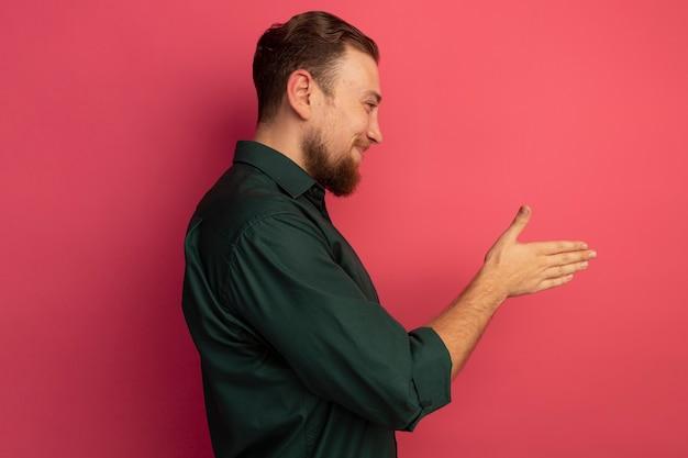 Heureux bel homme blond se tient sur le côté en tenant la main isolée sur un mur rose