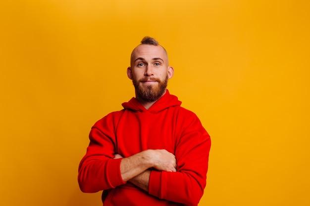 Heureux bel homme brutal bearder portant un sweat à capuche polaire tendance hiver rouge chaud