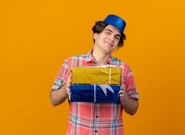 Heureux bel homme caucasien portant un chapeau de fête bleu détient des coffrets cadeaux