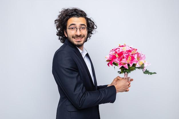Heureux bel homme en costume avec bouquet de fleurs à sourire gaiement