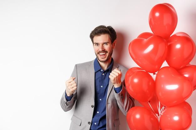 Heureux bel homme dansant et disant oui, debout près des ballons de coeur de jour d'amoureux et souriant, debout contre un fond blanc.