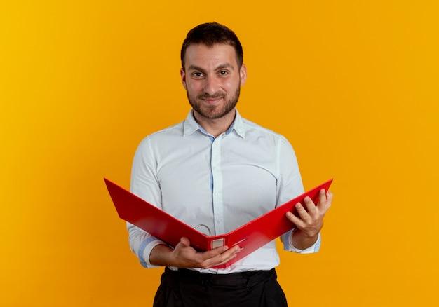 Heureux bel homme détient le dossier de fichiers isolé sur un mur orange