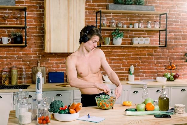 Heureux bel homme écoute de la musique dans les écouteurs et les danses, cuisine dans la cuisine à la maison.