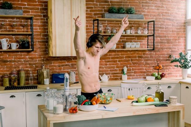 Heureux bel homme écoute de la musique dans les écouteurs et les danses, lève les mains, cuisine dans la cuisine à la maison.